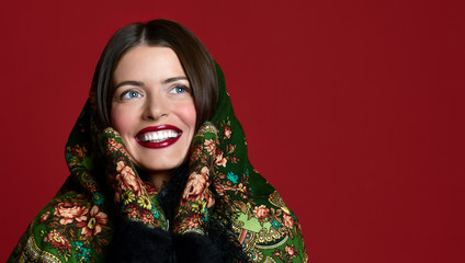 Portrait of High fashion glamour beautiful brunette hair Russian style woman in traditional scarf and gloves on red