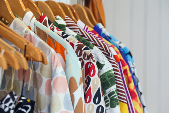 Variety of colorful shirts hanging on the wooden hangers, close up
