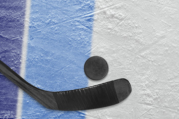 Hockey stick, puck and fragment of the ice arena with blue lines