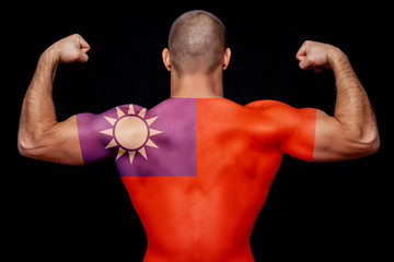The back of a young athletic man wearing a T-shirt with the national flag of Taiwan on a black isolated background. The concept of national pride and patriotism