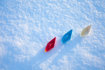 Red, blue and white paper boat in the snow