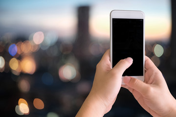 Smartphone on hands and empty device display on blur background city scape.