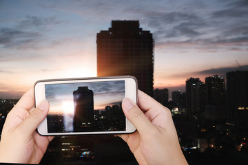 Hand using smartphone take a photo city scape at sunset time.