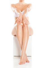 woman tenderly touching her legs on white background