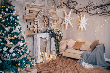 Christmas interior with a fireplace, a Christmas tree, gifts and a sofa. Wood and stone in the interior. Scenery for a photo studio.