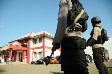 Mobile Police Brigade officers stand guard at the Lambaro prison after a riot and escape by more than 100 prisoners in Banda Aceh