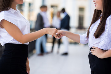Two beautiful businesswomen handshaking in office in front of business team. Succesful agreement at meeting