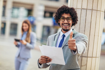 Cheerful african american business executive giving thumb up