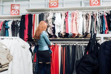 red hair young girl in a blue leather jacket chooses clothes in a store.