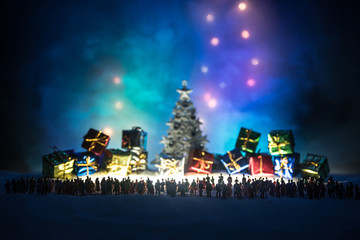 New year or Christmas holiday shopping concept. Store promotions. Silhouette of a large crowd of people watching at a big shopping trolley with gifts. People on snow prepares to shopping.