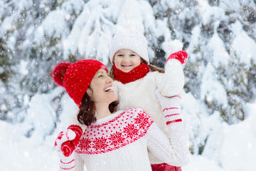 Mother and child in knitted winter hats in snow.