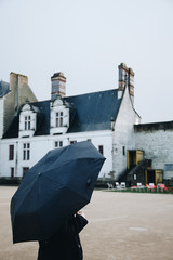 woman with umbrella looking the castle of Nantes in rainy day - France - Nantes FRANCE - NOVEMBER 2018