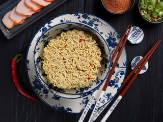 Ingredients for shin noodles in a blue bowl, with white and blue chopsticks, on dark blue background, top view