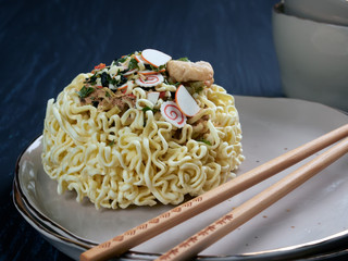 Ingredients for shin noodles in a blue bowl, with white and blue chopsticks, on dark blue background, closeup view