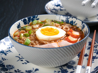 Bowl of shin noodles, with medium-boiled egg, slices of chicken breast and green scallions, close-up view