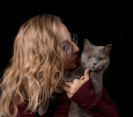 Portrait of a young woman with a cat on a black background
