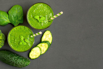 Two green smoothies with ingredients on dark background. Top view. With Copy space
