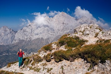 A mountaineer woman, happy to have successfully completed the climb of a mountain path.