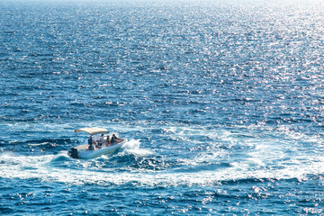 Motor boat with tourists on the sea surface.