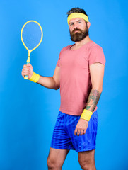 Tennis player retro fashion. Athlete hold tennis racket in hand on blue background. Tennis sport and entertainment. Tennis club concept. Man bearded hipster wear old school sport outfit with bandages