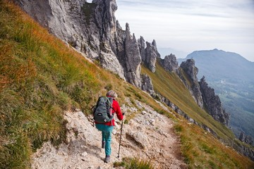 A woman hiker, descends from a steep trail of the Southern Grigna.