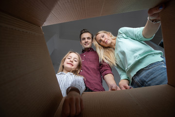 Photo of parents and daughter looking inside cardboard box