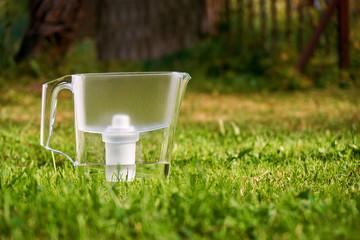 Water filter jug standing on the green grass in summer garden