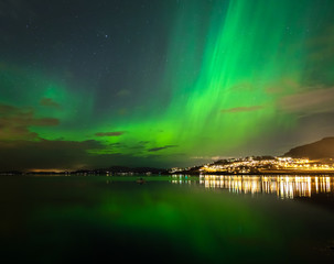 Green Aurora Borealis on night sky.