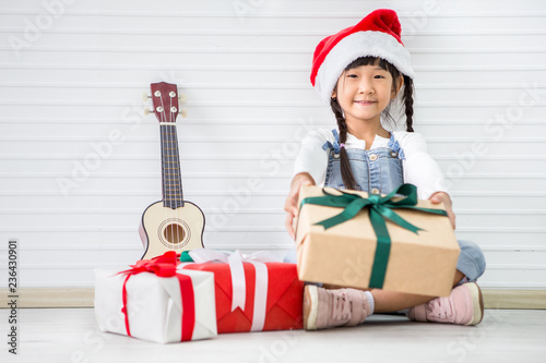 a6ae87dcfba93 asian girl in Christmas Santa hat show gift box with pile of presents and  Ukulele on white background . Chinese childen celebrating happy new year.  kid ...