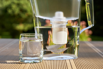 Plastic water filter pitcher and a clean glass of a clear water close up on the summer garden background