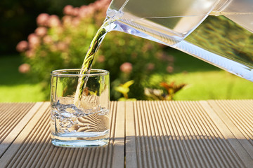 Pouring clear filtered water from a water filtration jug into a glass in green summer garden in a sunny summer day