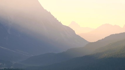 Wall Mural - Early morning shot of autumn mountains with colorful trees in first rays of sunlight of a new day.