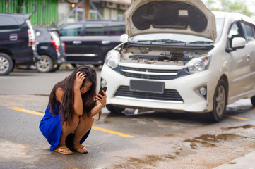 upset Asian Korean woman in stress stranded on street suffering car engine failure having mechanic problem calling on mobile phone for help to insurance assistance