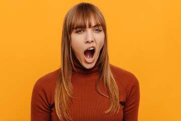Woman portrait. Emotion. Girl is yawning, on a yellow background