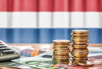 Fotomurales - Geldscheine und Münzen vor der Nationalflagge der Niederlande
