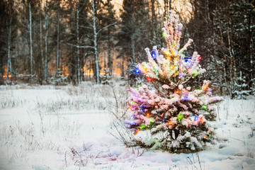 Christmas tree in fluorescent garland decorated in winter forest