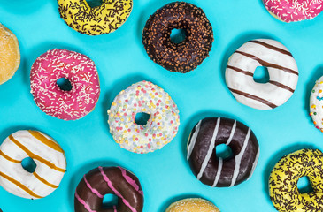 assorted donuts with different fillings and icing on a blue background. Top view.