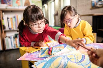 Girl having Down syndrome taking colorful marker from her teacher