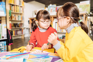 Sisters with Down syndrome coloring pictures in kids library