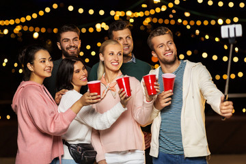 leisure, celebration and people concept - happy friends with drinks taking picture by selfie stick at rooftop party at night with blurred bokeh lights