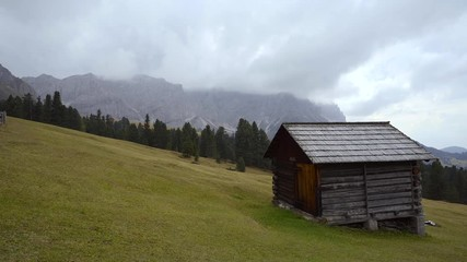 Fototapete - Wooden sheds on a grassy meadow on the edge of the forest with mountain rising in the background, Italian Dolomites.