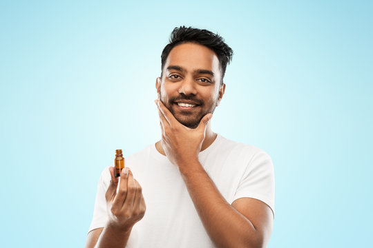 grooming and people concept - smiling young indian man applying lotion or beard oil over blue background