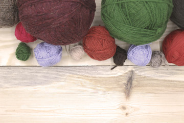 Knitting threads, balls of different colors on a wooden surface. Signature free space