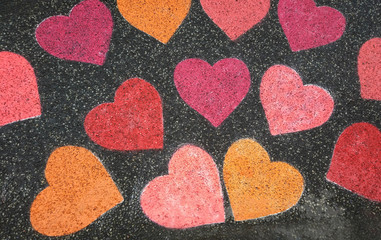 Hearts painted with colored chalk on the street.