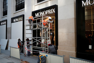 """Workmen protect a shop window against possible damage with wood panels on the eve of the """"yellow vests"""" protest against higher fuel prices on the Champs-Elysees Avenue in Paris"""