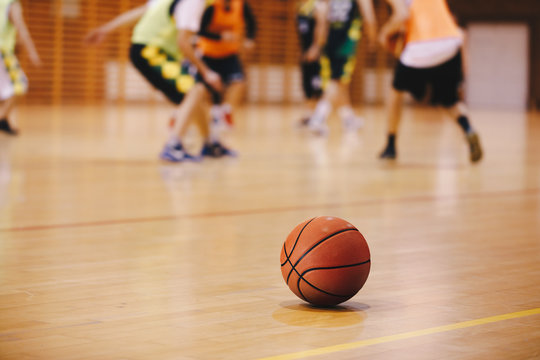 Basketball Training Game Background. Basketball on Wooden Court Floor Close Up with Blurred Players Playing Basketball Game in the Background