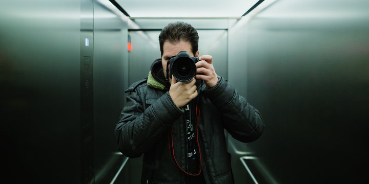 Photographer taking a cinematic mirror selfie with analog tungsten film look  and grain for ISO 800