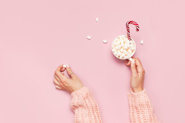Christmas New Year drink, white mug with marshmallows in female hands in knitted sweater and Candy Cane on pink background top view Flat Lay Winter traditional food. Festive decor, celebration Xmas