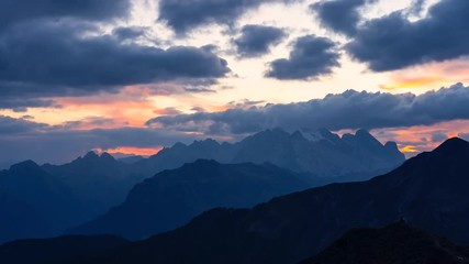 Wall Mural - Time Lapse footage of colorful sunset in Italian Dolomites with dramatic sky scape full of clouds turning orange to black.