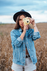Portrait of young woman wearing hat and denim jacket taking photo of viewer